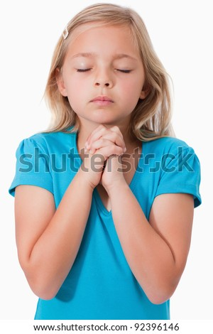 Portrait of a young girl praying against a white background - stock photo