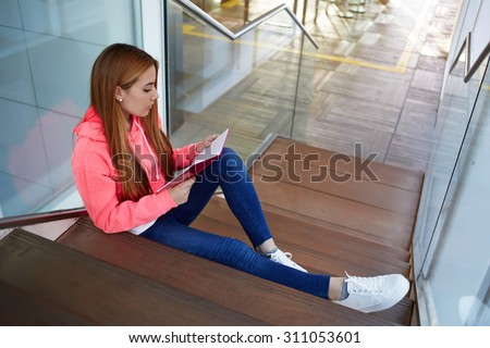 Portrait of a young girl reading the textbook while preparing for high school exams, college student preparing for class at campus, clever undergrad