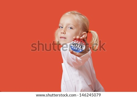Portrait of a young girl showing vote badge over pink background - stock photo
