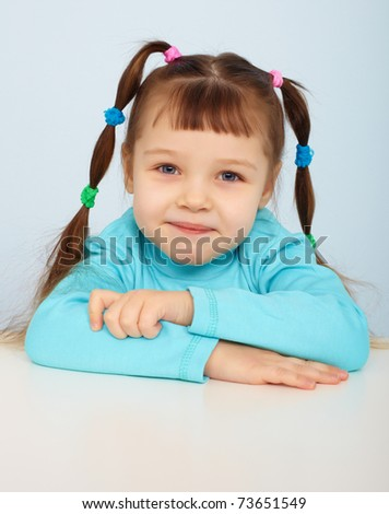 Portrait of a young girl sitting at the table - stock photo