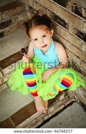 Portrait of a young girl sitting on brick steps eating a lollipop, wearing rainbow tights and a bright green tutu - stock photo