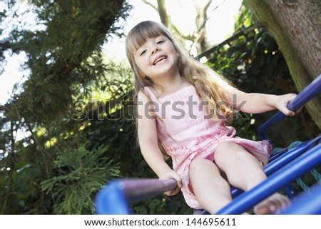 Portrait of a young girl sitting on monkey bars in the backyard - stock photo