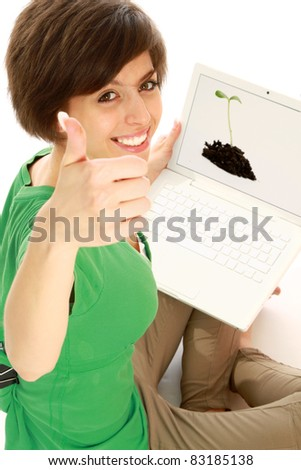 Portrait of a young girl sitting  with a laptop and showing thumbs up sign.  Top view - stock photo