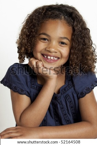 Portrait of a young girl smiling friendly with her face resting on her hand on a white background