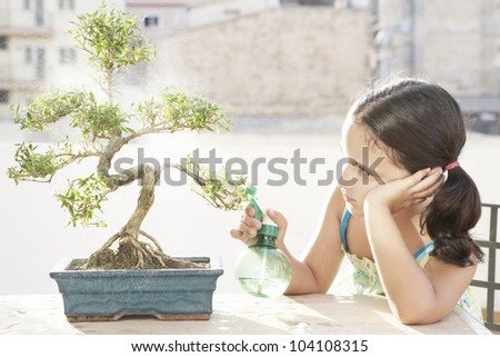 Portrait of a young girl watering a bonsai tree, feeling bored.