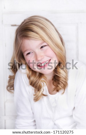 portrait of a young girl wear white looking of to side, smiling or laughing. - stock photo