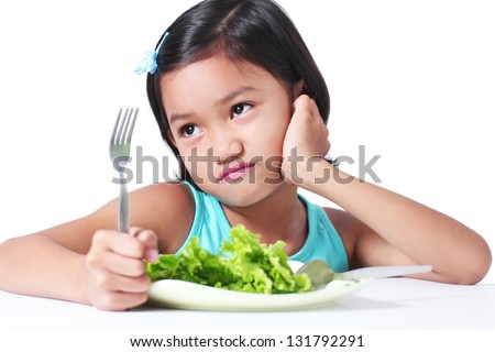 Portrait of a young girl who don't like eating vegetables. - stock photo