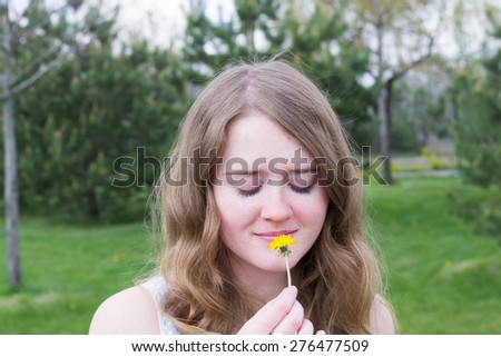 portrait of a young girl who with closed eyes smelling a daisy - stock photo