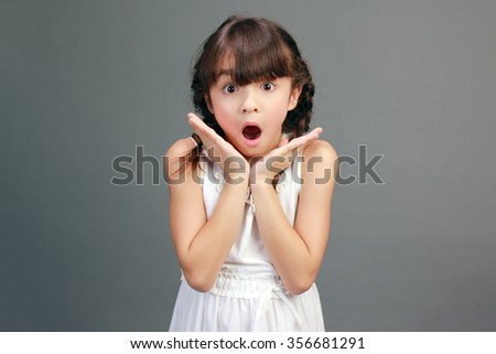Portrait of a young girl with a grey background. She is looking at the camera. - stock photo