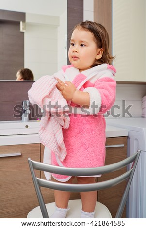 Portrait of a young girl with a towel in his hands after hand washing. The concept of health care, education. - stock photo