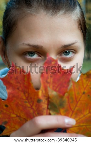 Portrait of a young girl with autumn leaves