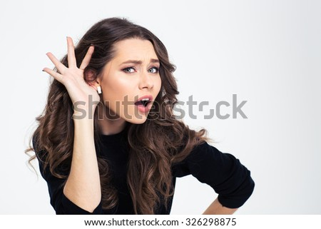 Portrait of a young girl with hand on ear. What did you say? - stock photo