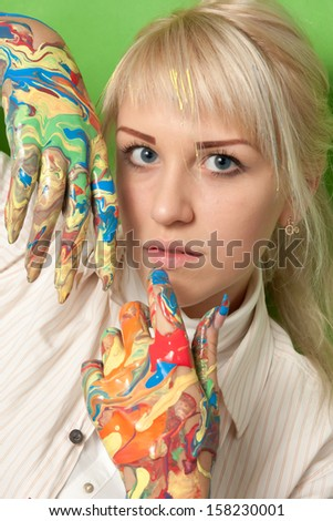 Portrait of a young girl with hands in fresh paint - stock photo