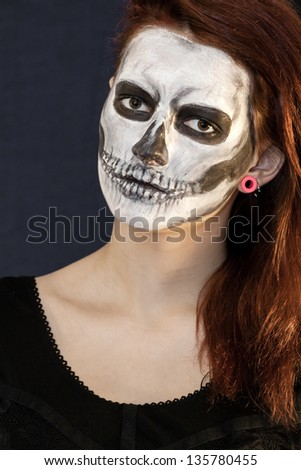 portrait of a young girl with skull mask painted on her face during halloween - Girl Halloween Masks