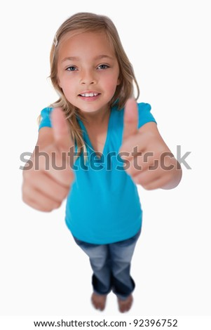 Portrait of a young girl with the thumbs up against a white background - stock photo