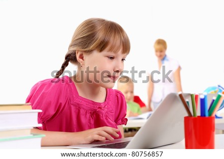 Portrait of a young girl working on laptop at school at the desk.