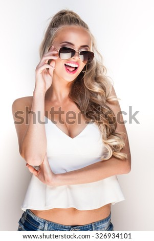 Portrait of a young glamorous lady in sunglasses posing near white wall
