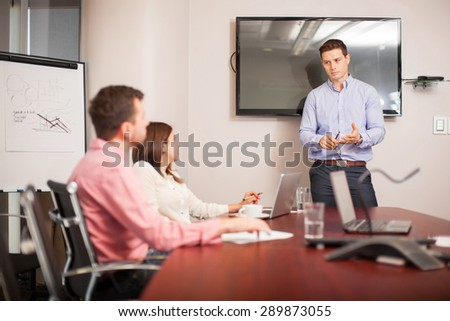 Portrait of a young good-looking man giving a business presentation to some clients - stock photo