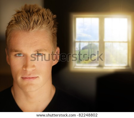 Portrait of a young good looking man with window in background - stock photo