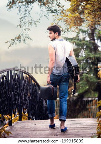 Portrait of a young guitarist walking away, view from back - stock photo