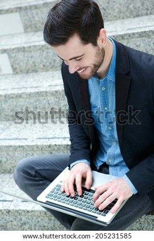 Portrait of a young guy smiling and using laptop - stock photo