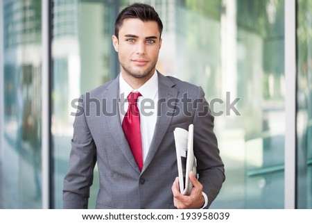 Portrait of a young handsome business man holding a newspaper - stock photo