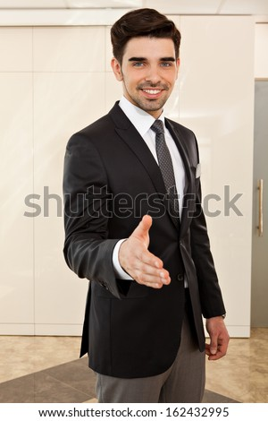 portrait of a young handsome business man smiling inviting to a handshake, focus on the face