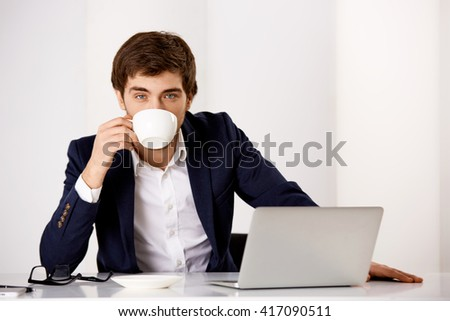 Portrait of a young handsome cheerful businessman in suit sitting at office at the desk having cup of coffee looking at camera. - stock photo