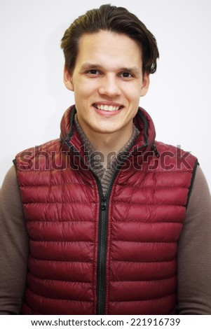 Portrait of a young handsome guy in the burgundy waistcoat - stock photo