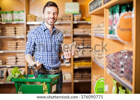 Portrait of a young handsome Hispanic man buying some healthy and organic food at a grocery store - stock photo