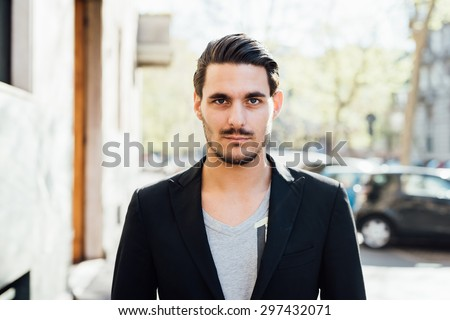 Portrait of a young handsome italian boy posing through the street of the city - stock photo