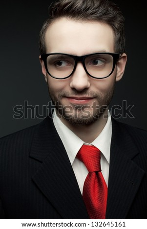 Portrait of a young handsome man (businessman) in black suit and trendy glasses smiling and looking at somebody or something. Close up. Studio shot