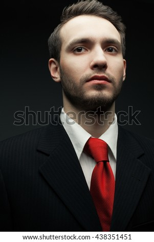 Portrait of a young handsome man (businessman) in black suit with trendy red tie. Trendy beard (bristle). Close up. Studio shot - stock photo