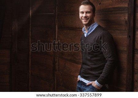 Portrait of a young handsome man fashion model on urban wooden background
