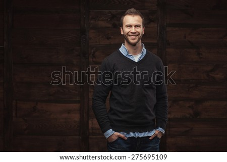 Portrait of a young handsome man fashion model over wooden background - stock photo