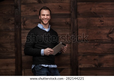 Portrait of a young handsome man fashion model with a tablet in urban background - stock photo