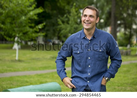 Portrait of a young handsome man in a blue shirt on the background of summer park - stock photo