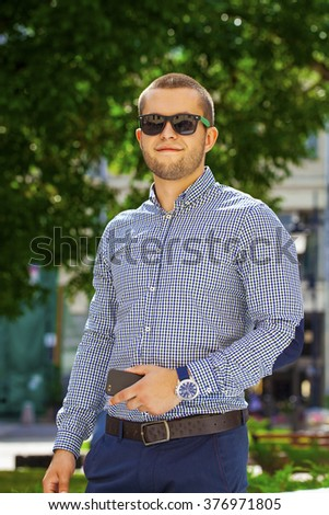 Portrait of a young handsome man in sunglasses on the background of summer street - stock photo