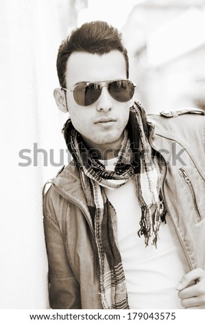 Portrait of a young handsome man, model of fashion, wearing tinted sunglasses in urban background. Tinted photograph - stock photo