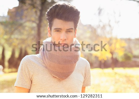 Portrait of a young handsome man, model of fashion, with modern hairstyle in the park - stock photo