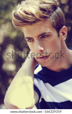 Portrait of a young handsome man, model of fashion, with modern hairstyle in urban background. Blonde hair - stock photo