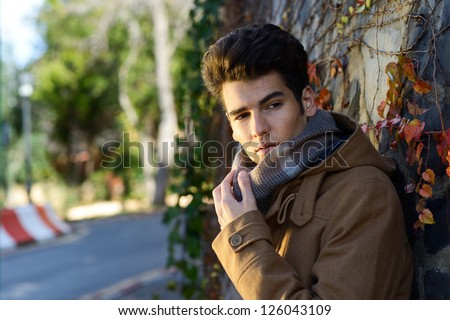 Portrait of a young handsome man, model of fashion, with toupee in a park - stock photo