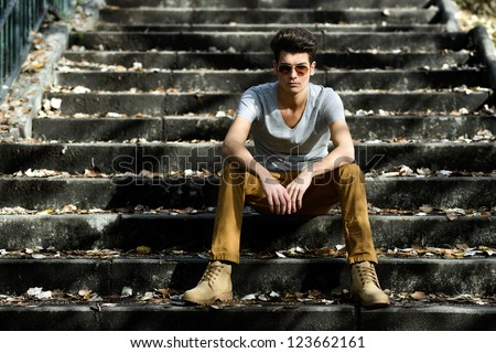 Portrait of a young handsome man, model of fashion, with toupee in stairs - stock photo