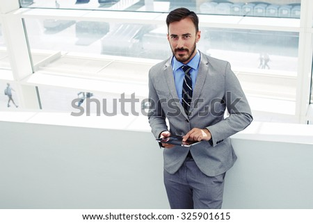 Portrait of a young handsome man office worker posing while standing with touch pad in modern office interior, confident male boos dressed in corporate clothing using digital tablet during work break  - stock photo