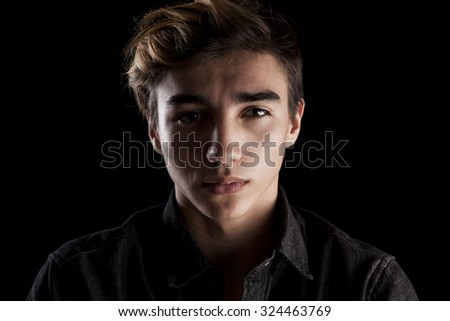 portrait of a young handsome man on black background - stock photo