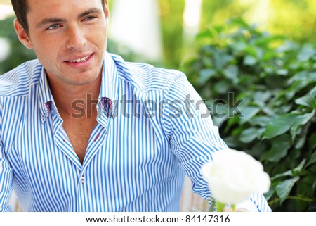 Portrait of a young handsome man passing a flower