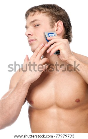 Portrait of a young handsome man shaving as part of his morning routin - stock photo