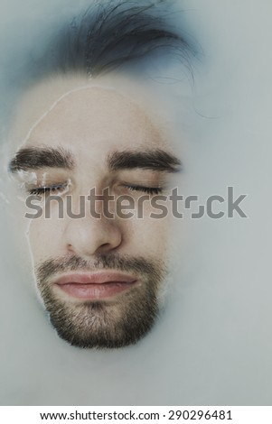 Portrait of a young handsome man taking a bath