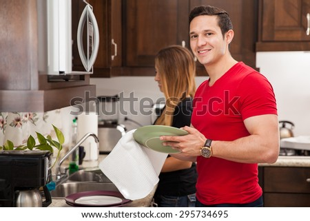 Portrait of a young handsome man washing the dishes with her wife at home