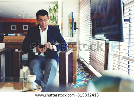 Portrait of a young handsome man watching the news on television during work on his mobile phone, successful managing director using cell telephone during coffee break in modern cafe inside  - stock photo